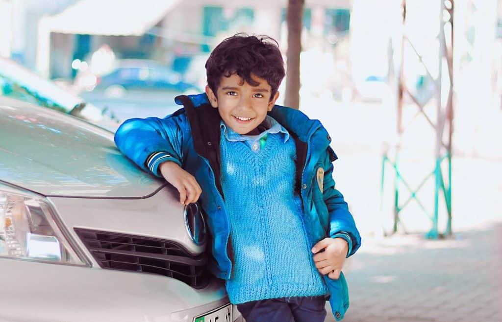 Little boy leans against car