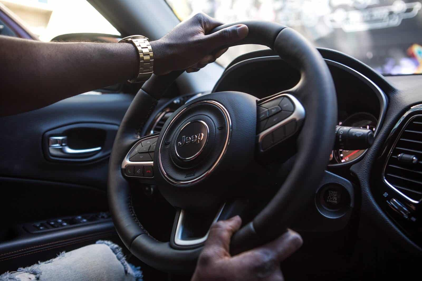 Person's hands on a Jeep steering wheel