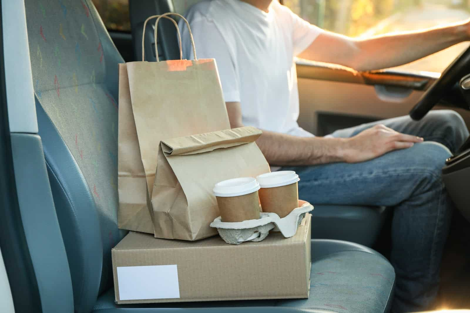 Postmates requirements: A driver with a food delivery on his passenger seat