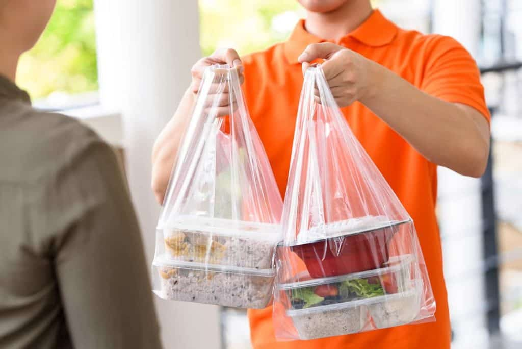 DoorDash fees: A delivery driver hands food to a customer